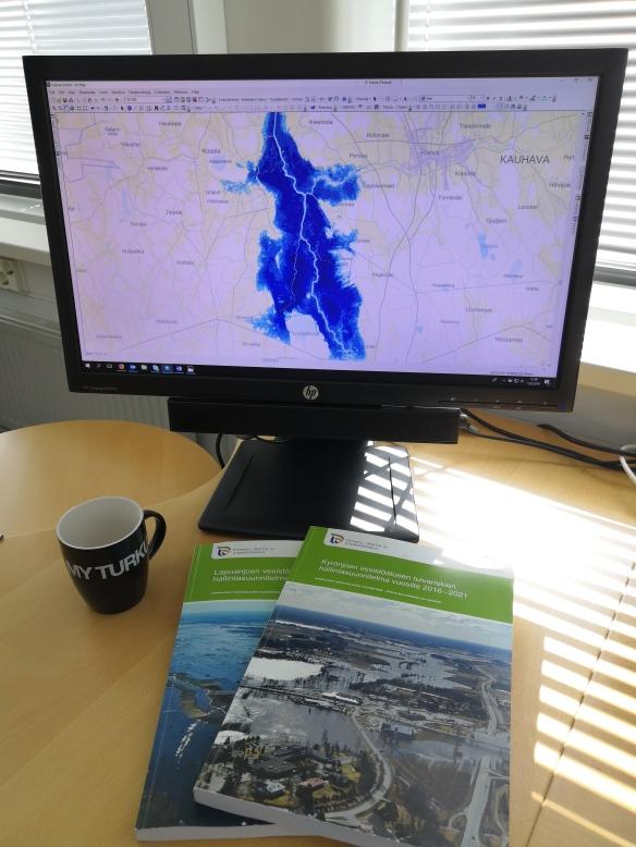 Kuvassa tietokoneen ruudulla tulva-aluetta kartalla, sekä kirjoja ja kahvikuppi.