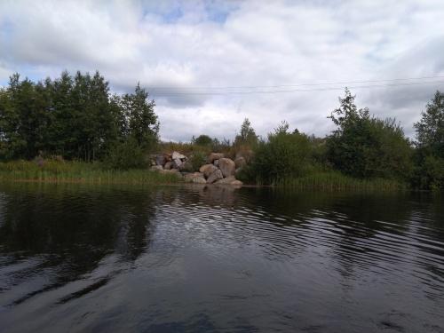 Kuvassa joen törmällä on kivikasa, joka sitoo maa-ainesta.
