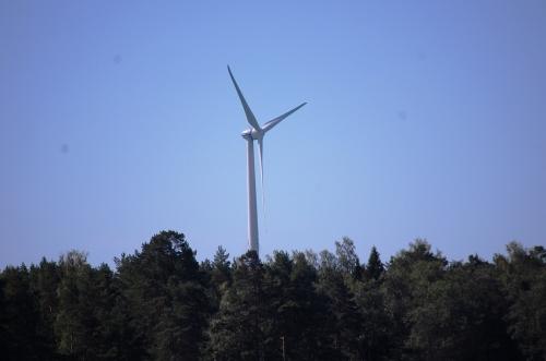 Tuulivoimalaitos kohoaa metsän yli korkealle.