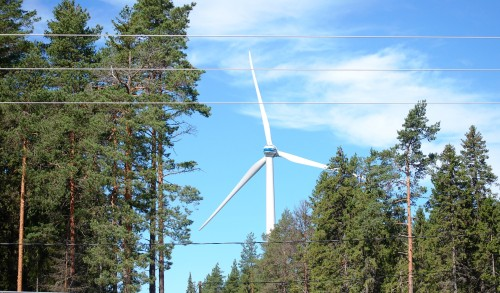 Tuulivoimala näkyy puiden välistä ja sähkölinjan takana.