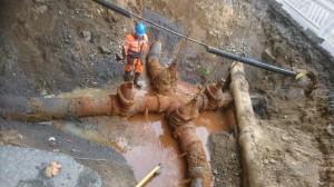 Kuvassa työmies seisoo kuopassa, jossa on kaivettu esiin vesijohtojen liittymäkohta.