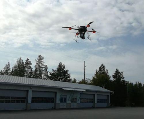 Drone-laite ilmassa ja taustalla näkyy pitkä rakennus.