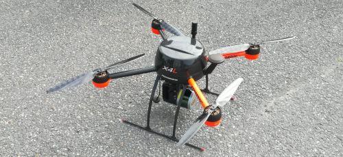 Lähikuva drone-laitteesta, joka on asfaltin päällä maassa.