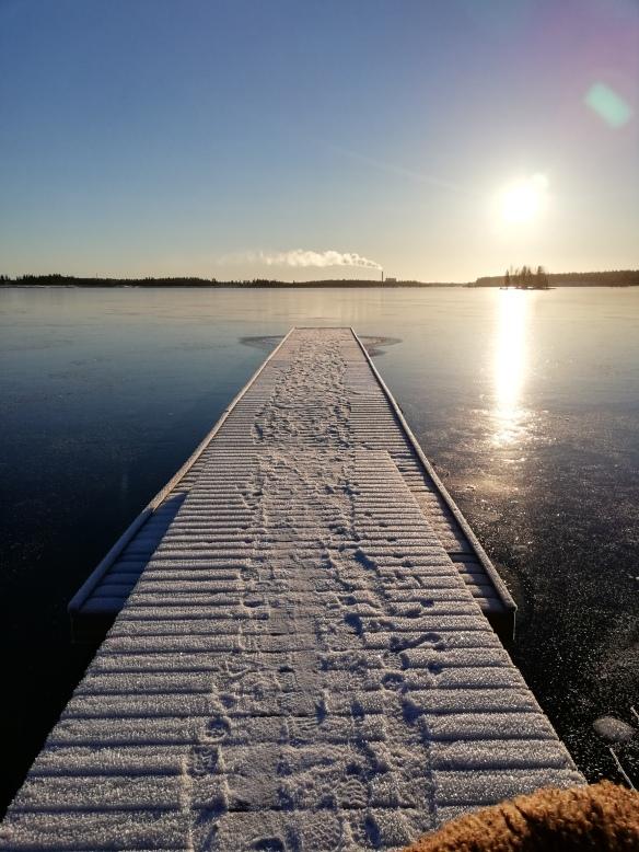 Talvinen laituri aurinkoisena päivänä.