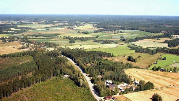 Ilmakuva peltomaisemasta, jota halkoo tie ja myös asutusta näkyy ja metsiä.