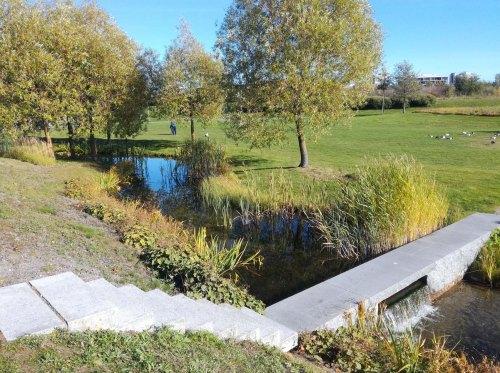 Puiston keskellä virtaa pieni joki tai puro, hohon on tehty ylikulkusilta betonista.
