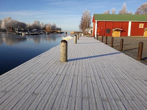 Talvinen meri, laituri ja venevaja sekä kirkas sininen taivas.