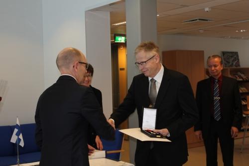 Kuvassa ylijohtaja luovuttaa Aulis Rantalalle korkea-arvoisen kunniamerkin, taustalla johtaja Aulis Östergård.