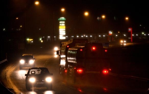 Pimeälla otettu kuva liikenteestä, näkyy autojen valoja ja pimeyttä.