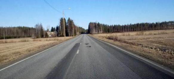 Kuvassa suoralla tiellä kaksi isoa kuoppaa asfaltissa.
