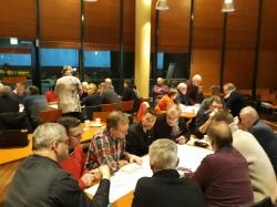 Ihmisiä pöytien ääressä pohtimassa tiehankkeen ympäristövaikutuksia.