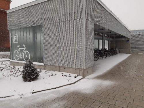 Kuvassa osaksi rakennusta on tety suojainen pyöräkatos.