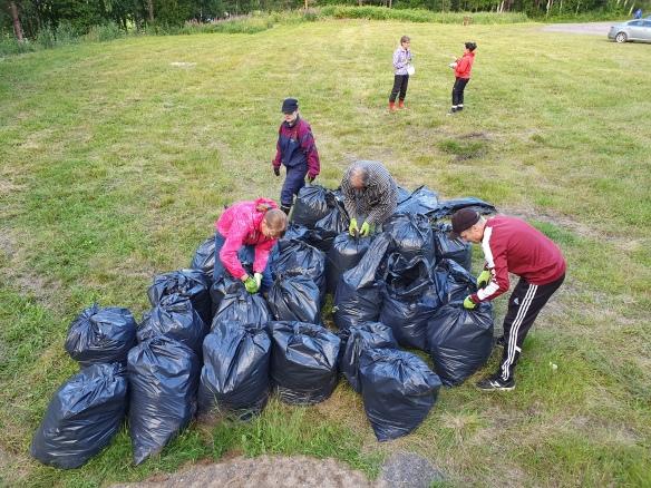 Talkoolaiset ovat kasanneet yhteen kasaan suuren määrän kitkettyjä kasveja sisältäviä jätesäkkejä.