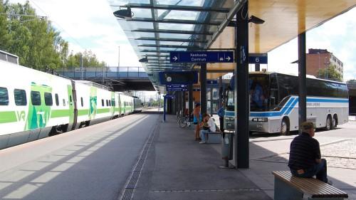 Juna, linja-auto ja ihmisiä Vaasan matkakeskuksessa.