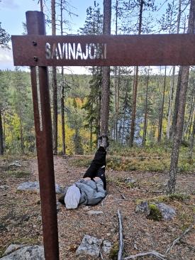 Savinajoen kyltti ja retkeilijä ottaa rennosti.