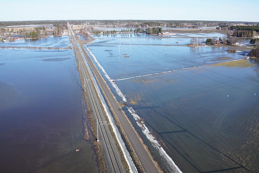 Suuri veden vallassa oleva alue, jonka keskellä kulkee maantie ja junarata.