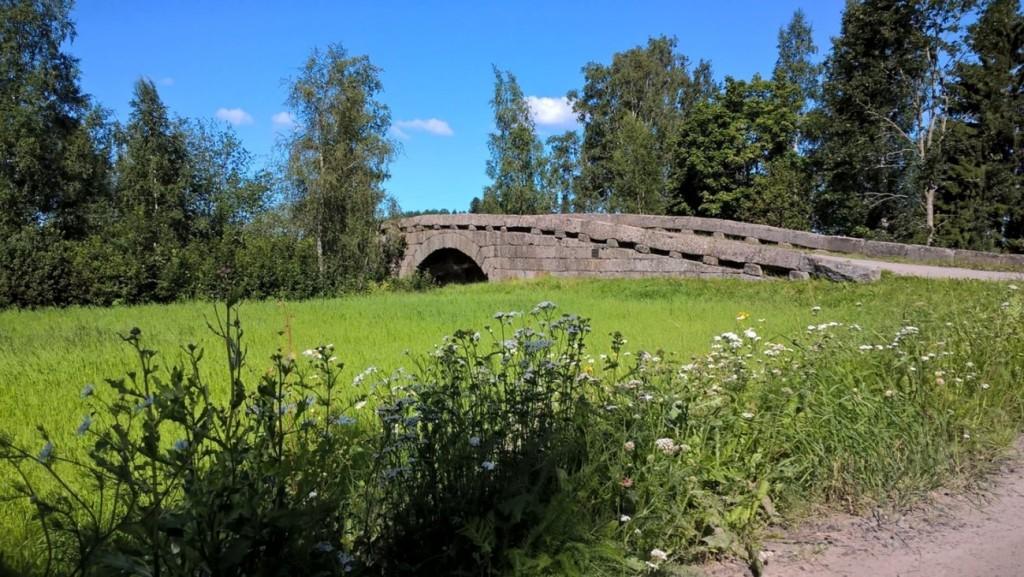 Kivinen silta kirkkaan vihreän ruohoalueen takana.