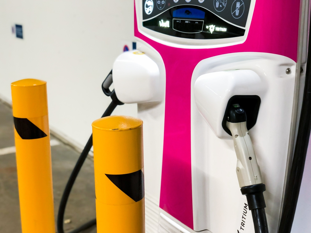 Lähikuva sähköauton latausasemasta. Asema on väriltään kirkkaan pinkki ja siihen on kiinnitetty kaksi latausjohtoa. Aseman etupuolella on kaksi oranssia metallitolppaa suojana.