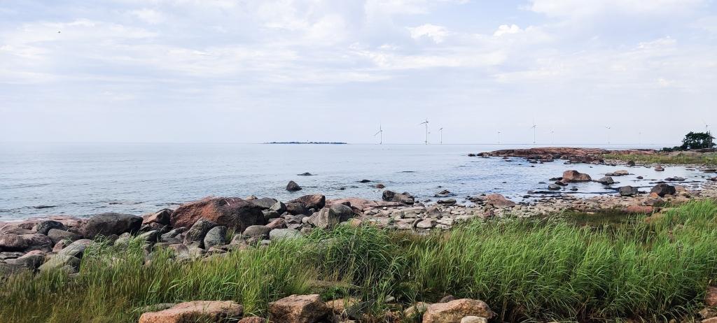 Pilvinen merimaisema, jonka horisontissa on tuulimyllyjä. Etualalla näkyy rantakiviä ja heinikkoa.