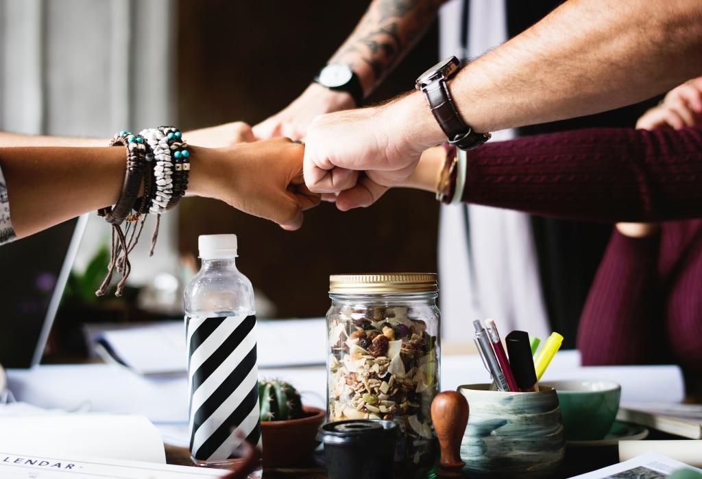 Viisi kättä yhdessä työpöydän yläpuolella. Pöydällä on työskentelytarvikkeita, jotka luovat vaikutelman keskeneräisestä projektista.