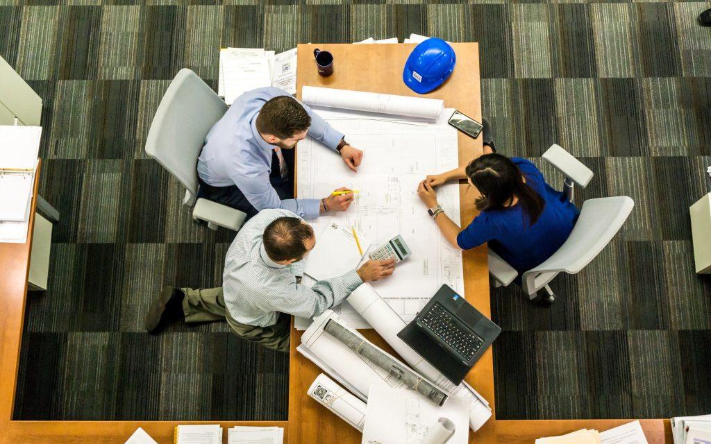 Ylhäältä kuvattu toimistossa sijaitseva työpöytä, jonka ääressä työskentelee kolme henkiöä. Pöydällä on kannettava tietokone, papereita, suojakypärä sekä muita työskentelyvälineitä.