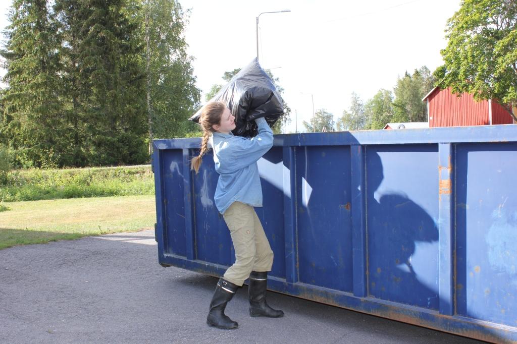 Kumisaappaisiin ja pitkiin vaatteisiin pukeutunut henkilö heittämässä jätesäkkiä suurelle siniselle jätelavalle.