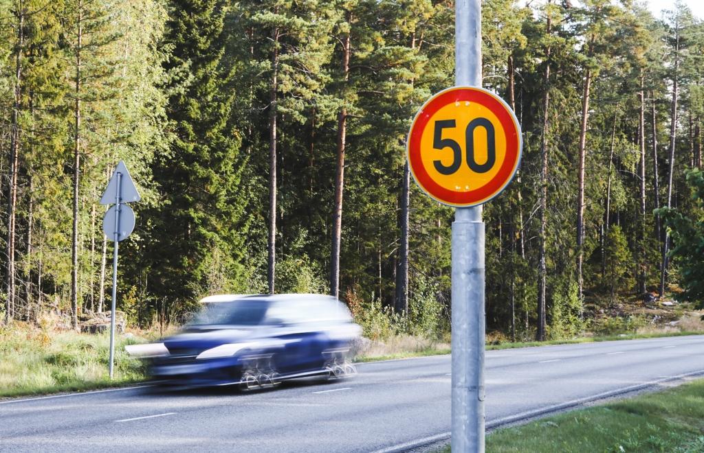 Valokuvan edustalla on 50 km/h nopeusrajoitusmerkki. Taustalla menee tie, jossa ajaa sininen henkilöauto.